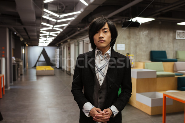 Asian man dressed in formal clothes standing indoors Stock photo © deandrobot