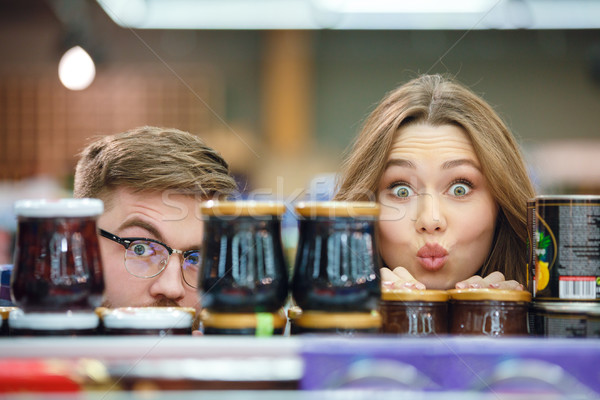 Couple looking camera hiding near marmelade Stock photo © deandrobot