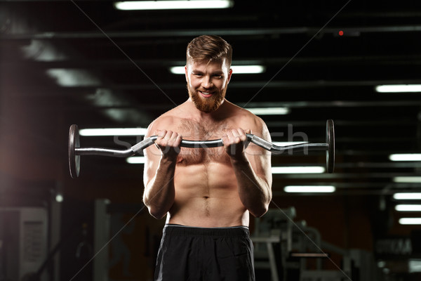 Happy sports man make sport exercises with barbell Stock photo © deandrobot