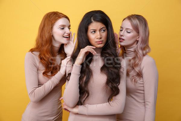 Két nő suttogás barát kettő fiatal nők citromsárga Stock fotó © deandrobot
