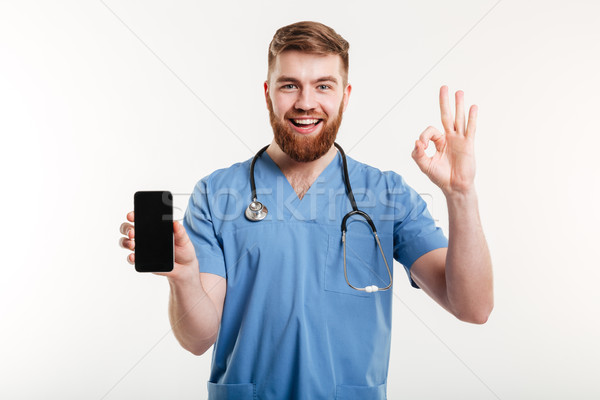 Male doctor smiling with phone and showing gesture Stock photo © deandrobot