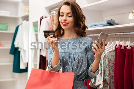 Sad curly young lady holding debit card. Looking aside. Stock photo © deandrobot