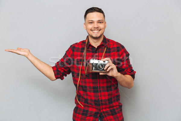 Smiling man holding copyspace on pound and retro camera Stock photo © deandrobot