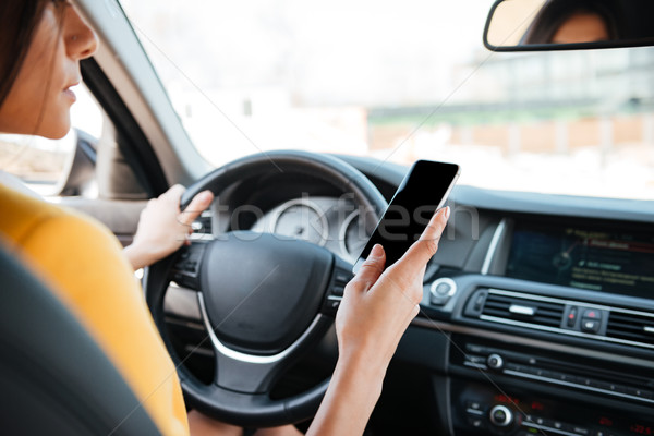 Young woman driver using touch screen smartphone Stock photo © deandrobot