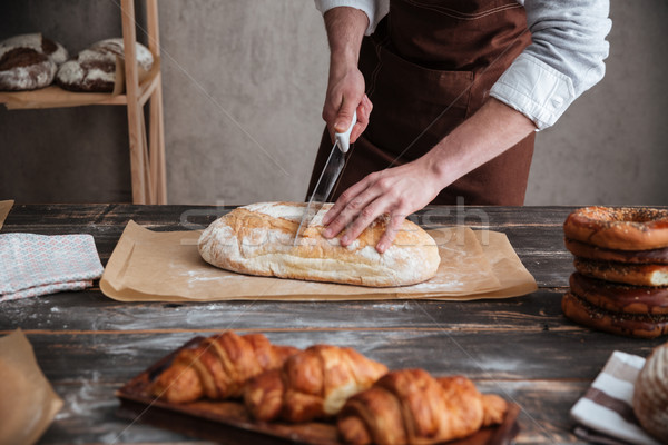 Cropped image of young man baker cut the bread. Stock photo © deandrobot