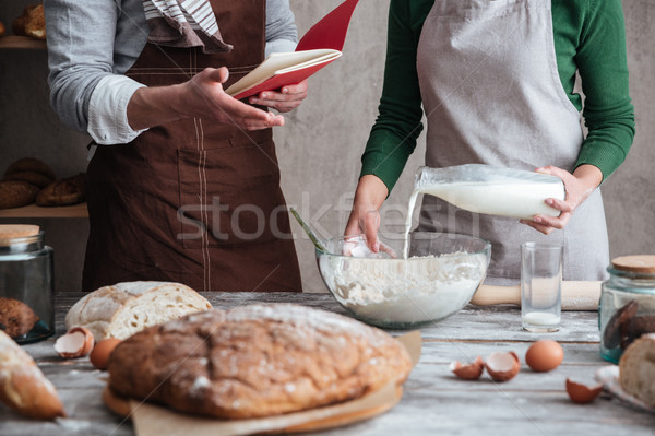 Loving couple bakers standing near bread and cooking. Stock photo © deandrobot