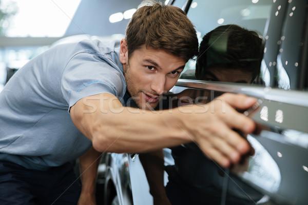 Young male customer examining a new car Stock photo © deandrobot