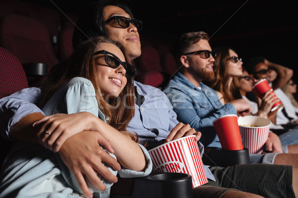 Loving couple sitting in cinema watch film and hugging Stock photo © deandrobot