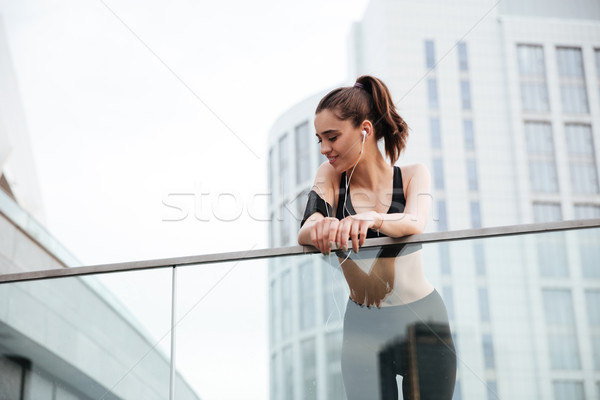Young sports lady standing with earphones outdoors Stock photo © deandrobot
