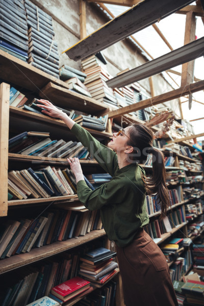 Woman in glasses getting book from high shelf Stock photo © deandrobot
