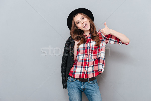 Excited stylish woman in plaid shirt showing thumbs up gesture Stock photo © deandrobot