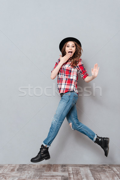 Portrait of an excited young woman in plaid shirt jumping Stock photo © deandrobot