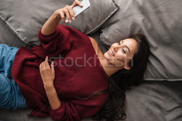 Top view of a smiling asian woman in sweater Stock photo © deandrobot