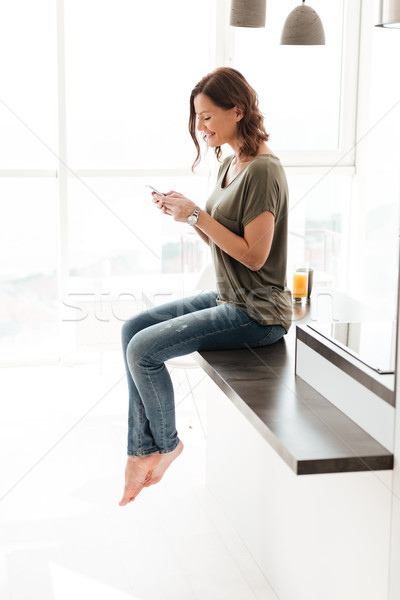 Side view of smiling woman sitting on table in kitchen Stock photo © deandrobot