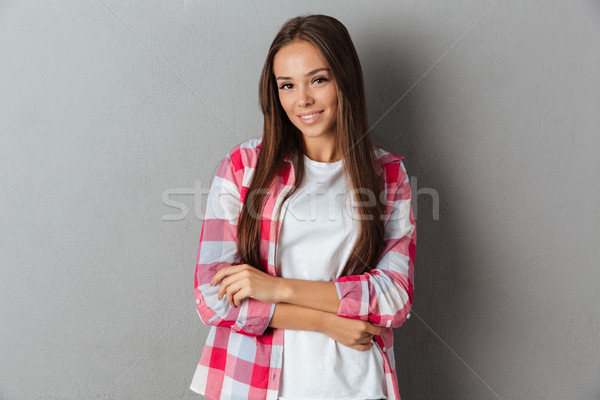 Pretty smiling girl in checkered shirt standing with arms folded Stock photo © deandrobot