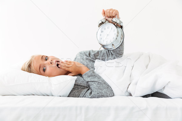 Amazed little blonde girl holding alarm clock, covering her mout Stock photo © deandrobot