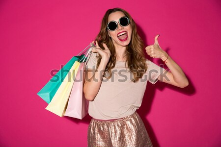 Pensive serious woman talking on phone and holding bags isolated Stock photo © deandrobot