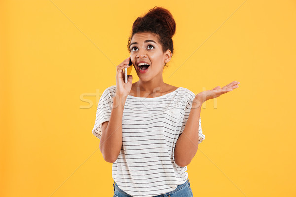 Happy african young woman with open mouth talking on phone isolated Stock photo © deandrobot