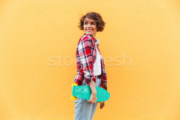Smiling young teenage girl holding skateboard Stock photo © deandrobot
