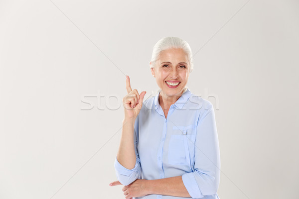 Laughing gray-haired old lady in blue shirt, pointing with finge Stock photo © deandrobot