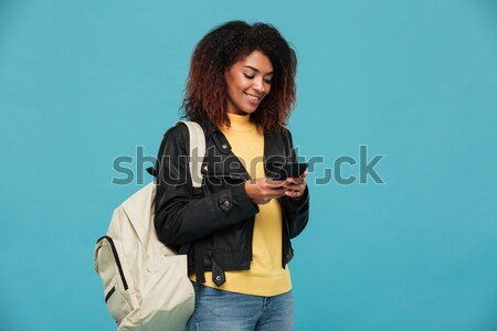 Pleased african woman in leather jacket with backpack Stock photo © deandrobot