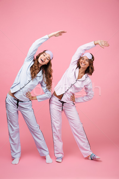 Stock photo: Happy two girls friends make stretching exercises in pajamas