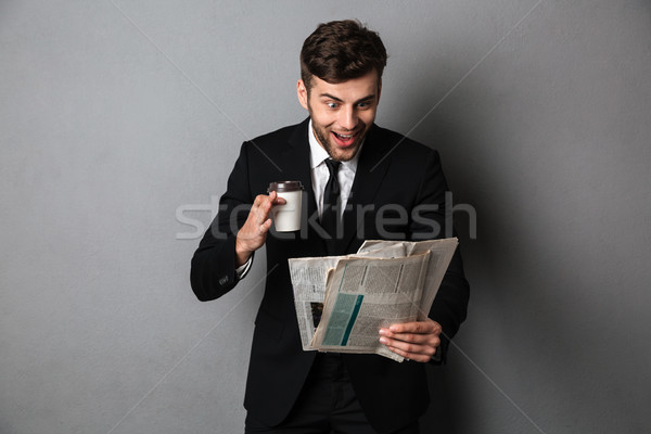 Happy exited handsome businessman reading newspaper and holding  Stock photo © deandrobot