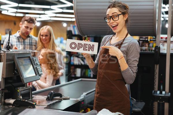 Portret uśmiechnięta kobieta kasjer wskazując palec Zdjęcia stock © deandrobot