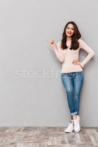 Full-length photo of cheerful brunette woman pointing index fing Stock photo © deandrobot