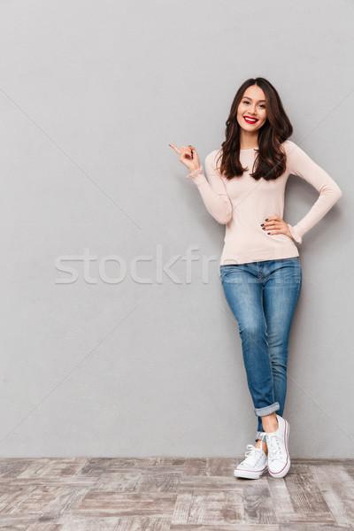 Fotografia wesoły brunetka kobieta wskazując Zdjęcia stock © deandrobot