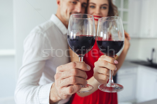 Close up of glasses with wine holding by pretty couple Stock photo © deandrobot