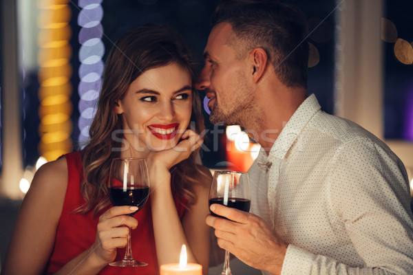 Young handsome man whisper to his woman while have romantic dinner Stock photo © deandrobot