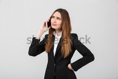 Thoughtful brunette lady talking on smartphone Stock photo © deandrobot