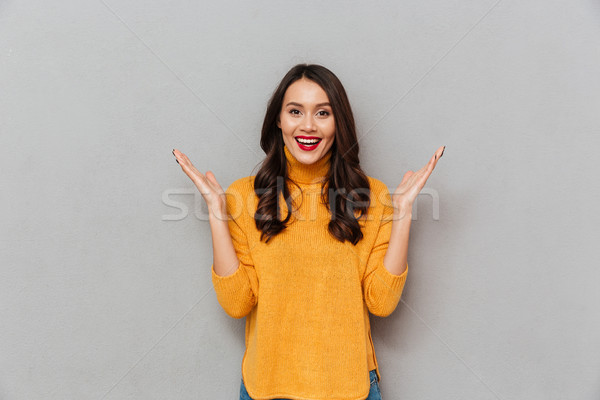Surpreendido satisfeito morena mulher suéter olhando Foto stock © deandrobot