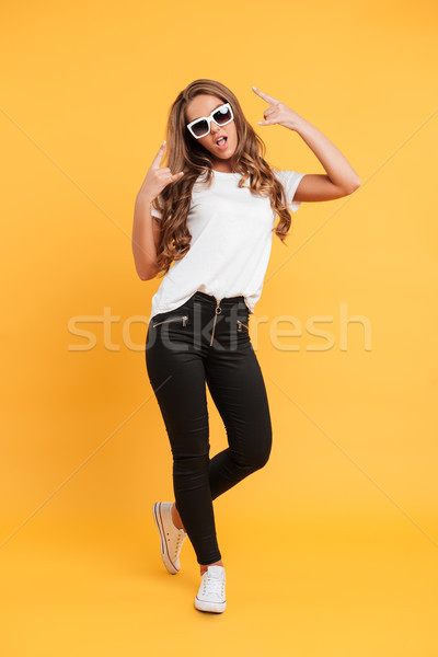 Amazing pretty young woman showing rock gesture. Stock photo © deandrobot