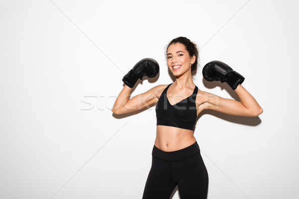 Smiling curly brunette fitness woman in boxing gloves showing biceps Stock photo © deandrobot