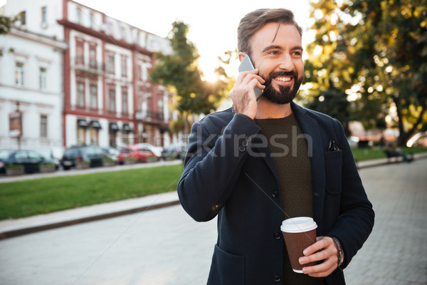 Portrait of a cheerful attractive man talking on mobile phone Stock photo © deandrobot