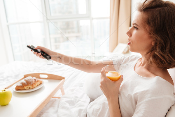 Side view picture of serious young lady watch tv Stock photo © deandrobot