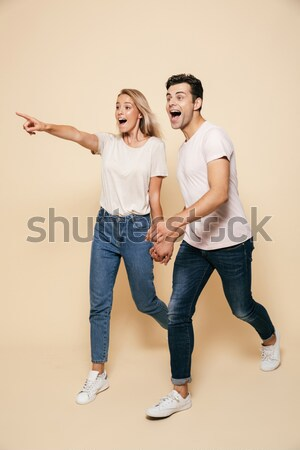 Full length image of pleased couple man and woman 20s in denim c Stock photo © deandrobot