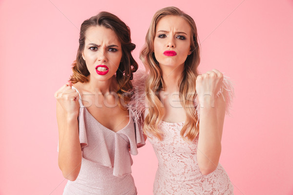 Two angry women in dresses hugging to each other Stock photo © deandrobot
