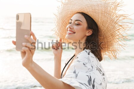 Photo of joyous blonde woman 20s smiling, and taking photo of su Stock photo © deandrobot