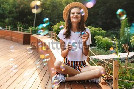 Izgatott fiatal lány fúj szappanbuborékok park kint Stock fotó © deandrobot