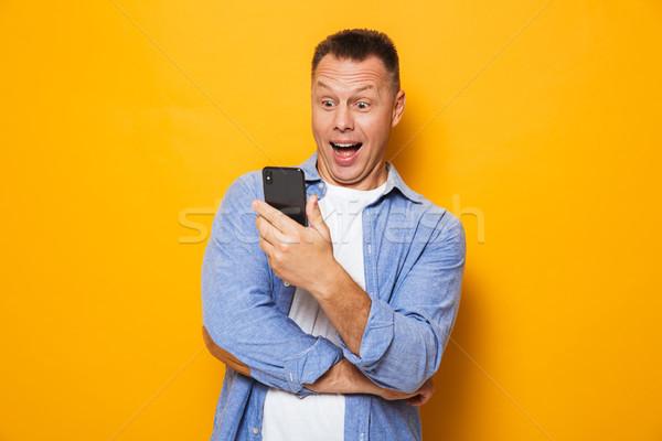 Portré izgatott középkorú férfi néz mobiltelefon izolált Stock fotó © deandrobot