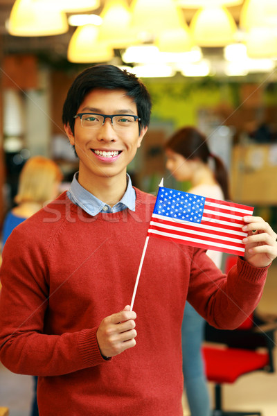 Cheerful asian student holding flag of USA Stock photo © deandrobot