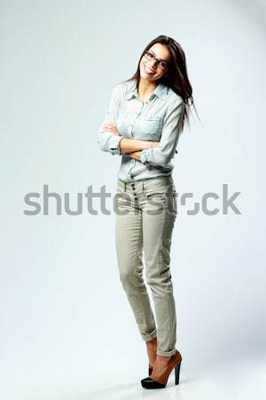 Full-length portrait of a young smiling woman with arms folded isolated on gray background Stock photo © deandrobot
