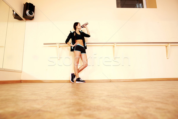 Full-length portrait of a young fit woman drinking water at gym Stock photo © deandrobot