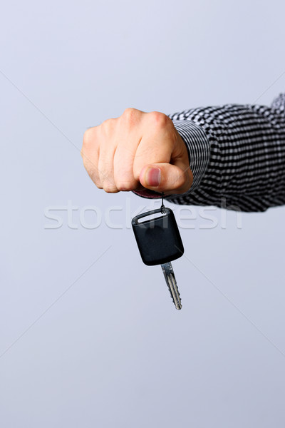 Hand holding car keys isolated on gray background Stock photo © deandrobot