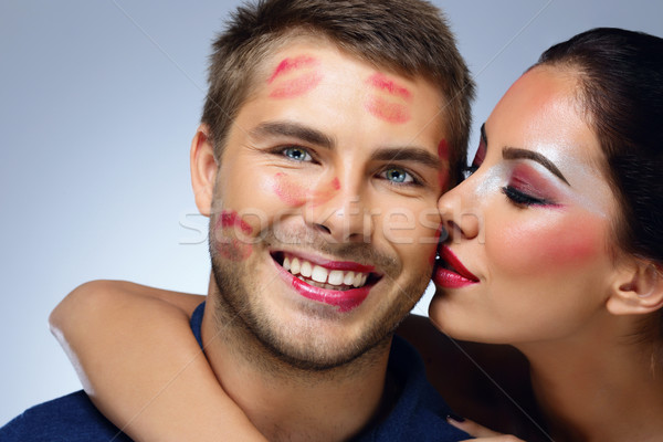 Beautiful woman kissing happy man over blue background Stock photo © deandrobot