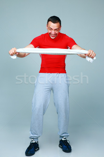Full length portrait of a crazy sports man with towel on gray background Stock photo © deandrobot
