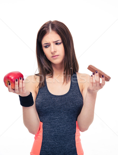 Sports woman making choice between apple and chocolate Stock photo © deandrobot